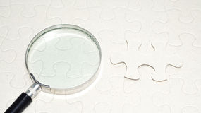 Magnifier with empty puzzle.concept photo. Stock Photos