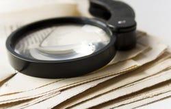 Magnifier en krant Stock Foto's