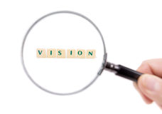 Magnifier enlarges the word vision. Stock Photos