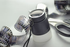 Magnifier and film. Films and photograpycs instruments: magnifier and scissor royalty free stock photography