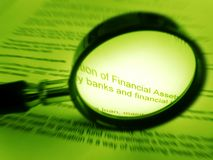 Magnifier and financial documents. A concept image of a magnifying glass used in studying of a finance document. Metaphor picture for studying the small fine Stock Photo