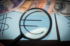 Magnifier focused on the Euro sign, on a background of euro, dollar, reminbi banknotes Stock Images