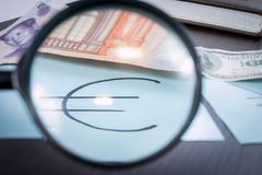 Magnifier focused on the Euro sign, on a background of euro, dollar, reminbi banknotes Stock Photos