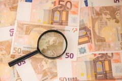 Magnifier focused on Europe. Euro banknotes. Magnifier on euro cash. Royalty Free Stock Photo