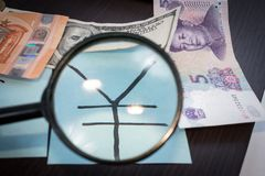 Magnifier focused on the Yuan Renminbi sign, on a background of international money. Stock Photos