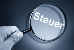 Magnifier with german word Steuer Stock Photography