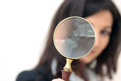 Magnifier glass. Young business woman looks through a magnifier glass isolated over whute background Stock Images