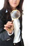 Magnifier glass. Young business woman looks through a magnifier glass isolated over whute background Royalty Free Stock Images