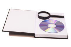 Magnifier glass, book and DVD Stock Photos