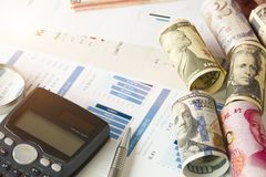 Magnifier glass calculator and financial data on businessman `s desk for analysis and find the best stock from stock market