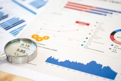Magnifier glass and financial data on businessman `s desk for analysis and find the best stock from stock market.