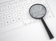 Magnifier glass on the keyboard Royalty Free Stock Photos