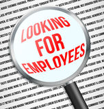 Magnifier glass over Looking for employees text Royalty Free Stock Photo