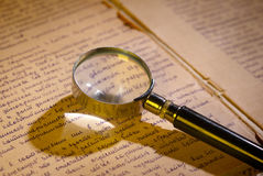 Magnifier glass on page of ancient manuscript. Old newspaper. Small depth of field Stock Photos