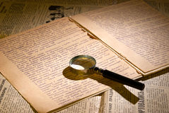 Magnifier glass on page of ancient manuscript. Old newspaper. Small depth of field Stock Photography