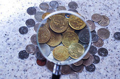 Magnifier glass with pile of coins,concept photo. Group of coins with single stack coins Royalty Free Stock Image