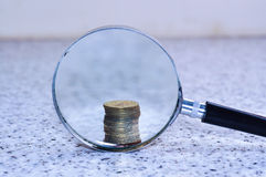 Magnifier glass with single stack of coins,concept photo. Magnifier glass with single stack coins Royalty Free Stock Photos