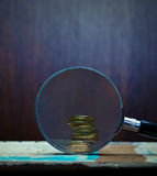 Magnifier and gold coins. Royalty Free Stock Photos