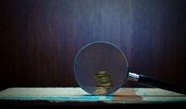 Magnifier and gold coins. View of magnifier and gold coins concept Stock Photos