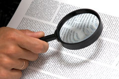 Magnifier in hand Stock Photo