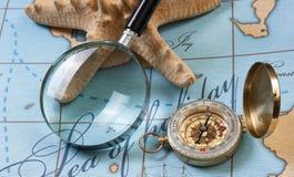 Magnifier i kompas na mapie zdjęcia stock