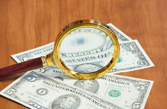 The magnifier  lays on dollars Stock Photo