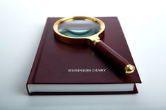 Magnifier lies on a business diary on a white table Royalty Free Stock Photography
