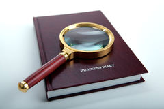 Magnifier lies on a business diary on a white table Stock Photos