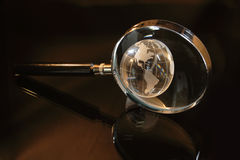 Magnifier and little globe royalty free stock image