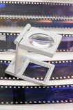 Magnifier loupe over transparency film slide. Royalty Free Stock Images