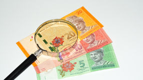 Magnifier with Malaysia bank notes.concept photo. Royalty Free Stock Photo