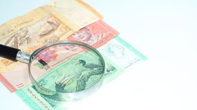 Magnifier with Malaysia bank notes.concept photo. Royalty Free Stock Photos
