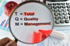 Magnifier on meaning of TQM with document, calculator and marker Stock Photos