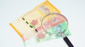 Magnifier met de bankbiljetten van Maleisië De foto van het concept Stock Foto's