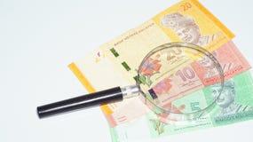 Magnifier met de bankbiljetten van Maleisië De foto van het concept Stock Afbeelding