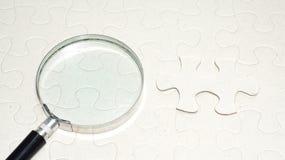 Magnifier met leeg raadsel De foto van het concept Stock Foto's