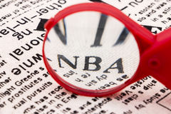 Magnifier NBA. The red magnifying glass enlarged the NBA on the newspaper Royalty Free Stock Photos
