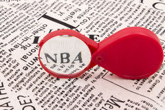 Magnifier NBA. The red magnifying glass enlarged the NBA on the newspaper Stock Photography