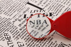 NBA newspaper. The red magnifying glass enlarged the NBA on the newspaper Royalty Free Stock Photo