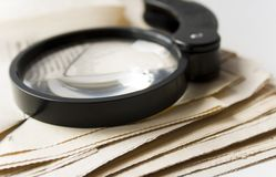 Magnifier and newspaper Stock Photos