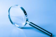 Magnifier no azul imagem de stock royalty free