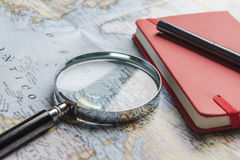 Magnifier, notebook and pen on map Royalty Free Stock Photo