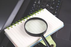 Magnifier on notepad on black notebook keyboard stock images