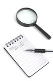 Magnifier and notepad with pen Stock Photo