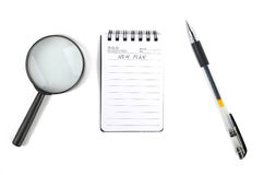Magnifier and notepad with pen Royalty Free Stock Photos