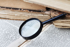 Magnifier and old books. Magnifying glass lying on open book Stock Photography
