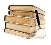Magnifier and old books Stock Photos
