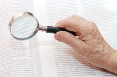 Magnifier in old hand Stock Image