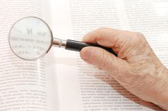 Magnifier in old hand Stock Photography