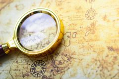 Magnifier on old map background. stock photos